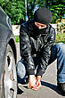 Man In Mask Punctures A Car Tyre. Revenge Concept stock photo