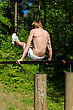 Man Pull-ups On A Bar In A Forest. From The Back. stock photo