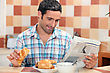Man Reading The Newspaper While Having Breakfast stock photography