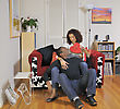 Man Sitting On The Floor As Part Of A Mixed-race Couple Handing Up A Box Of Chocolates To His Seated Wife. stock photo