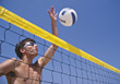 Man Spiking Volleyball Over Net stock photo
