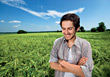 Man Standing In Green Field Smiling stock photo