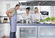 Man & Two Women In Kitchen, Him Putting On Apron stock photo