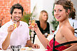 Man And Woman Holding Champagne Glasses In Restaurant stock photo