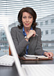 Mature Business Woman Sitting At Her Desk stock photo
