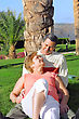 Mature Couple Lying In Embrace And Looked At Each Other With Love. In Tropical Resort