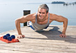 Smiling Mature Man Doing Push-ups stock photography