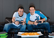 Men Sitting on Couch Playing Video Game stock photo