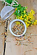 Metal Strainer With Dry Flowers Tutsan, Fresh Flowers Tutsan Against A Wooden Board stock image