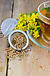 Healing Metal Tea Strainer With Dry Flowers Tutsan, Fresh Flowers Of Hypericum , Tea In A Glass Cup On A Wooden Boards Background stock photo