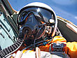 Aviation Military Pilot In The Plane In A Helmet In Dark Blue Overalls Against The Blue Sky stock photo