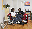 Mixed Race Couple Enjoy A Romantic Moment Sitting Together On A Small Sofa stock image