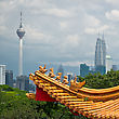 Fragment Mixture Of Architectural Styles In Kuala Lumpur, Malaysia. The Roof Of Ancient Chinese Temple On The Background Of Two Symbols Of Kuala Lumpur - KL Tower And Petronas Twin Towers. stock photography