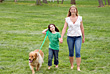 Mom and Daughter Walking Dog