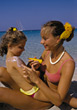 Mom rubbing lotion on her daughter at the beach stock photography
