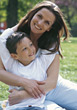 Mother and Son Sitting on Grass stock photo