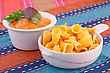 Nachos And Cheese Sauce On Colorful Towels stock photo
