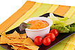 Nachos, Cheese Sauce, Vegetables On Brown Plate On Colorful Towels stock photo