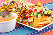 Nachos, Vegetables And Cheese Sauce On Colorful Towels