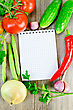 Notebook, Red Tomatoes, Red Hot Pepper, Parsley, Garlic, Onion, Cucumber, Green Bean Pods On An Old Wooden Board