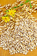 Oat Flakes With Yellow Wild Flowers And Stems Of Oats On A Wooden Board stock photo