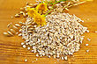 Oatmeal With Yellow Wild Flowers And Stalks Of Oats Against A Wooden Board stock photography