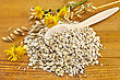 Oatmeal With Yellow Wild Flowers And Stalks Of Oats, A Wooden Spoon Against The Wooden Board stock photography