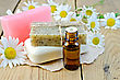 Oil In A Bottle, Homemade Soap On A Piece Of Paper, Daisy Flowers On A Background Of Wooden Boards