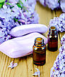 Oil In A Bottle, Soap, Lilac Flowers On The Background Of Wooden Boards stock image