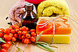 Oil In A Bottle, Two Homemade Soap, Towels, Twig And Berries Of Sea Buckthorn On A Wooden Board stock photo