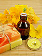 Oil In A Bottle, Two Homemade Soaps, Nasturtium Flowers, Yellow Candle On A Bamboo Mat stock photography