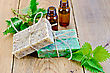 Oil In Bottles, Two Bars Of Homemade Soap With Twine, Nettle On The Background Of Wooden Boards