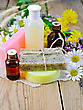 Oil And Lotion Bottles, Homemade Soap On A Piece Of Paper, Chamomile Flowers, Tansy, Elecampane On The Background Of Wooden Boards stock photo