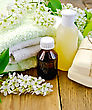 Twine Oil And Lotion Bottles, Soap, Flowers Bird Cherry, A Towel On The Background Of Wooden Boards stock photo