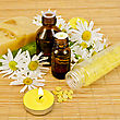Oil In Two Different Bottles, Two Homemade Soap, Bath Salt, Two Candles With Flames And Chamomile Flowers On A Bamboo Mat stock photo