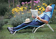 Old Man On Lounge Chair Reading Newspaper stock photo
