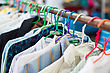 Old Shirt Hanging On Plastic Hangers In Second Hand Maket stock photo