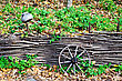 One Cartwheel The Fence, The Old Cast Iron Pot On A Background Of Trees, Green Grass And Yellow Autumn Leaves