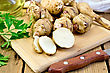 One Cut And A Few Whole Tubers Of Jerusalem Artichoke With Parsley, Knife And Vegetable Oil Decanter On A Wooden Board stock photo