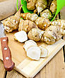 One Cut And A Few Whole Tubers Of Jerusalem Artichoke With A Bucket, A Knife And A Sacking On A Wooden Board stock photo