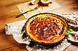 Onion Pie Or Tart Served With Grilled Halves Of Onion And Fresh Herbs. Rustic Style. Close Up View. Image Toned In Warm Colors stock photo