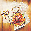 Onion Pie Or Tart Served With Grilled Halves Of Onion And Fresh Herbs On Wooden Table. Rustic Style. Top View. Image Toned With Vintage Colors stock image