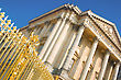 Palace Facade With Columns And Golden Gate In Versailles Over Blue Sky. France