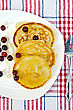 Pancakes With Cranberries And Honey On A White Plate, Fork On Napkin Background