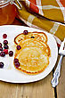 Pancakes With Cranberries And Honey On A White Plate, A Jar Of Honey, Fork, Napkin On The Background Of Wooden Boards