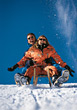 winter vacation sledding snow couple relaxing stock photo