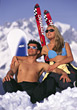 winter vacation sitting tanning snow couple stock photo