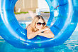 Pensive Blond Woman Posing With Rubber Ring In Swimming Pool stock photography
