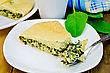 Pie With Spinach And Cheese On A Plate, Spinach Leaves, Cup, Fork, Napkin On The Background Of Wooden Boards