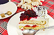 Piece Of Cake With White Cream And Red Jelly On The Plate, A White Porcelain Cup Of Coffee With Two Lumps Of Sugar, White Coral On A Background Of Red Plaid Fabric stock photo